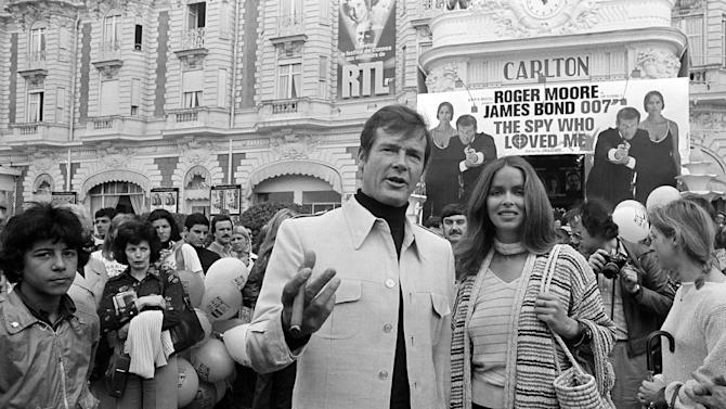 "FILE - In this May 20, 1977 file photo, actor Roger Moore, alias British secret agent James Bond, is accompanied by co-star Barbara Bach as they arrive for the screening of their latest 007 feature, ""The Spy Who Loved Me,"" during the Cannes Film Festival at the French Riviera. Moore, played Bond in seven films, more than any other actor. (AP Photo, File)"