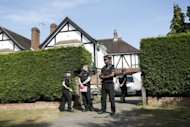 British police stand outside the Claygate home of a family shot dead in their car in the French Alps. French police were on Monday waiting to question a young British girl seen as the key to solving the mystery of the shooting that left three members of her family and a cyclist dead