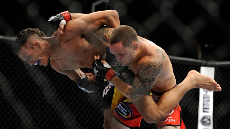 Frankie Edgar throws Charles Oliveira to the mat during their UFC 162 mixed martial arts featherweight bout at the MGM Grand Garden Arena on Saturday, July 6, 2013, in Las Vegas. Edgar won the fight by an unanimous decision. (AP Photo/David Becker)