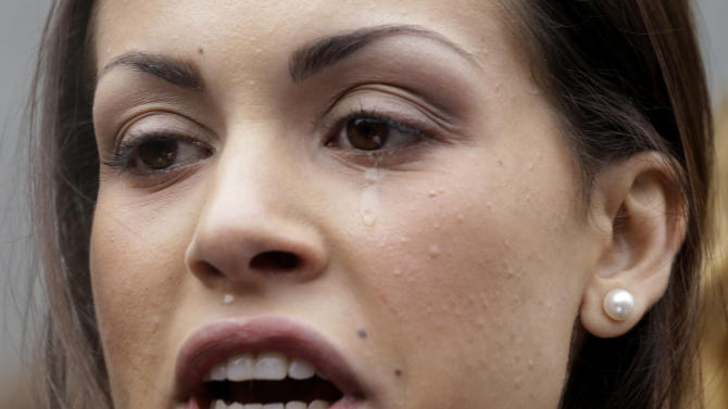 A tear rolls down the cheek of Karima el-Mahroug, also known as Ruby, a Moroccan woman at the center of ex-Premier Silvio Berlusconi's sex-for-hire trial, as she reads a statement to reporters during a protest outside the court house, in Milan, Italy, Thursday, April 4, 2013. The Moroccan woman at the center of ex-Premier Silvio Berlusconi's sex-for-hire trial has denounced what she says is psychological warfare being waged against her by Italian prosecutors. Ruby, read out a lengthy statement Thursday to a gaggle of reporters in front of Milan's courthouse denying she was a prostitute and insisting that prosecutors hear her side of the story. (AP Photo/Luca Bruno)