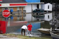 People stand amidst receding floodwaters from Hurricane Isaac in Scaresdale , La., Sunday, Sept. 2, 2012. More than 200,000 people across Louisiana still didn't have any power five days after Hurricane Isaac ravaged the state. Thousands of evacuees remained at shelters or bunked with friends or relatives. (AP Photo/Gerald Herbert)
