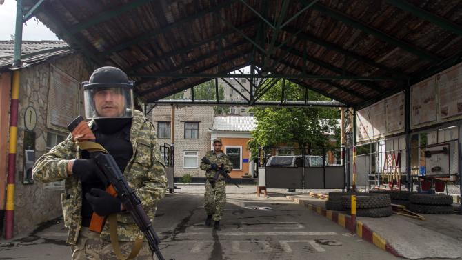 Pro-Russian armed men walk in an entrance to a border guards base, which they seized, on the outskirts of Luhansk, Ukraine, Wednesday, June 4, 2014. Pro-Russian insurgents in eastern Ukraine have taken two government bases in battles around Luhansk, seizing quantities of ammunition and explosives from a border guards post and taking another installation after National Guard forces ran out of ammunition. (AP Photo/Igor Golovniov)