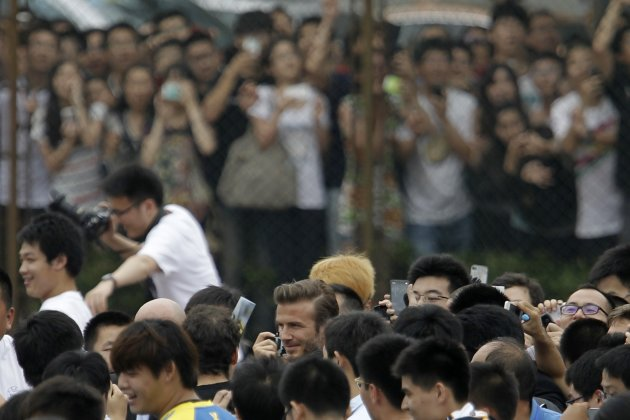 Former England captain David Beckham arrives at Tongji University surrounded by his fans in Shanghai