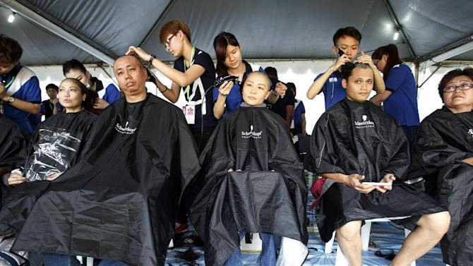 """Participants get their heads shaved during an event called """"Jom Botak"""" or """"To Go Bald"""" in Putrajaya, Malaysia, Saturday, Nov. 1, 2014. The event is to raise awareness and funds for cancer. (AP Photo/Lai Seng Sin)"""