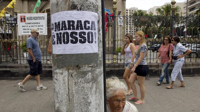 "Pedestrians walk past a pole displaying a poster that reads in Portuguese; ""Maraca is ours,"" near a protest against the privatization of the Maracana stadium, also known as Maraca, in Rio de Janeiro, Brazil, Saturday, Dec. 1, 2012. About 500 people, including Indians and students, protested Saturday, against privatization of the stadium because it will lead to the demolition of a nearby museum and a public school. (AP Photo/Silvia Izquierdo)"