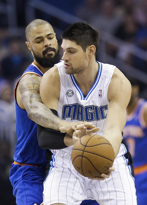 New York Knicks' Tyson Chandler, left, reaches out to try to steal the ball from Orlando Magic's Nikola Vucevic, right, of Montenegro, in the first half of an NBA basketball game in Orlando, F