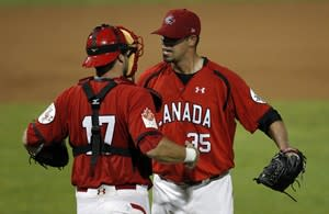 Canada's reliever Dustin Molleken, right, celebrates with the catcher Emerson Frostad after getting the last out during the seventh inning of a Baseball World Cup second round game against South Korea in Aguadulce, Panama, Thursday Oct. 13, 2011. Canada's Molleken and Scott Mathieson have returned from careers in Japan to play in the World Baseball Classic. THE CANADIAN PRESS/AP-Andres Leighton