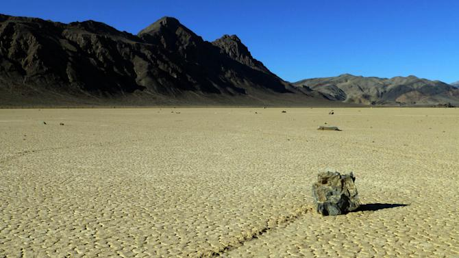 """This undated photo provided by the National Park Service shows rocks that have moved across a dry lake bed in Death Valley National Park in California's Mojave Desert. For years scientists have theorized about how the large rocks — some weighing hundreds of pounds — zigzag across Racetrack Playa leaving long trails etched in the earth. Now two researchers at the Scripps Institution of Oceanography have photographed these """"sailing rocks"""" being blown by light winds across the former lake bed. Cousins Richard Norris and James Norris say the movement is made possible when ice sheets that form after rare overnight rains melt in the rising sun, making the hard ground muddy and slick. (AP Photo/National Park Service)"""