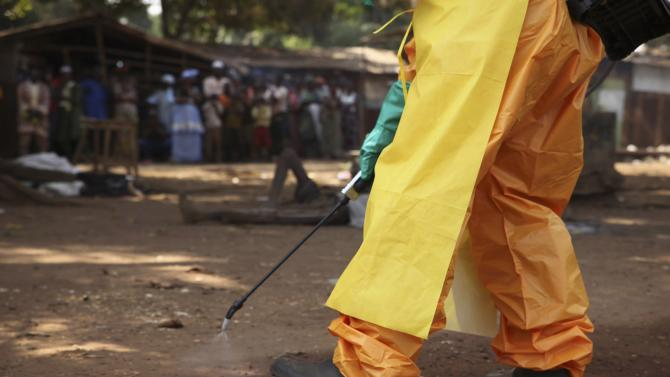 A member of the French Red Cross disinfects the area around a motionless person suspected of carrying the Ebola virus as a crowd gathers in Forecariah