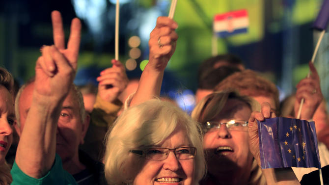 People take part in celebrations marking Croatia's entry into the European Union, on the central square in Zagreb, Croatia, late Sunday, June 30, 2013. Croatia has become the 28th member of the European Union, a major milestone some 20 years after the small country won independence in a bloody civil war that shook the continent. (AP Photo/Darko Bandic)