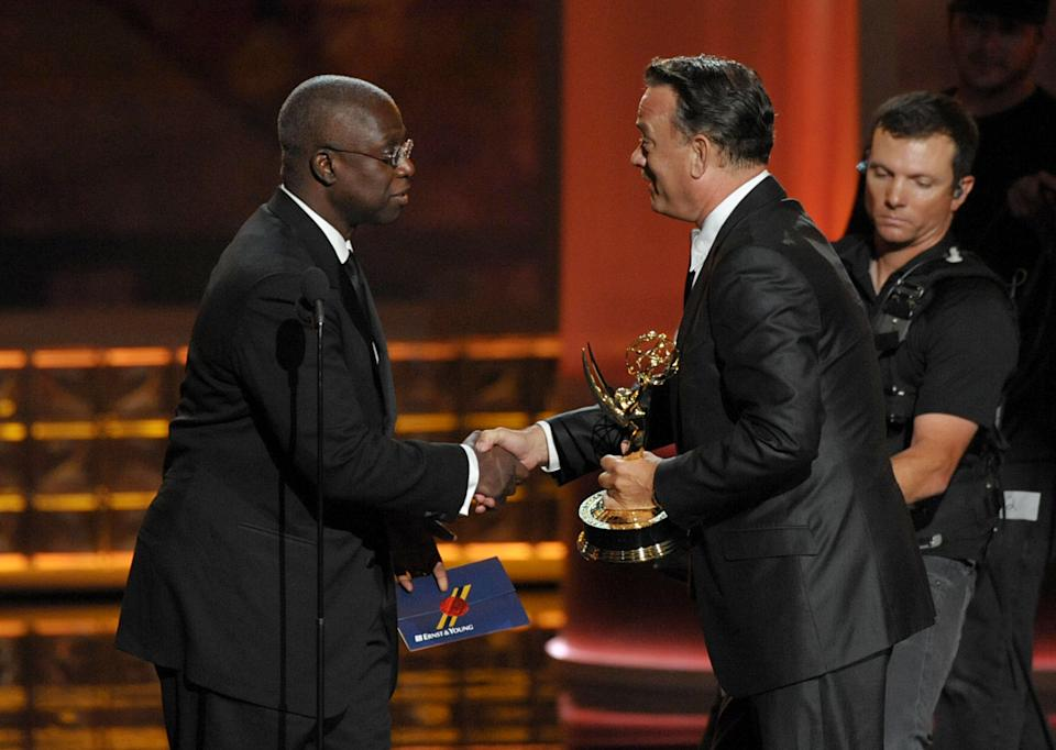 "Andre Braugher, left, presents the award for Outstanding Miniseries Or Movie to Tom Hanks for ""Game Change"" at the 64th Primetime Emmy Awards at the Nokia Theatre on Sunday, Sept. 23, 2012, in Los Angeles. (Photo by John Shearer/Invision/AP)"