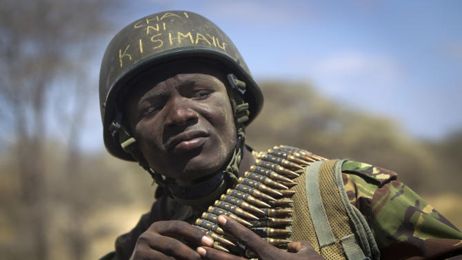 "FILE - In this Tuesday, Feb. 21, 2012 file photo, Kenyan army soldier Nicholas Munyanya, wearing a helmet on which is written in Kiswahili ""Tea in Kismayo"", referring to a key strategic Somali town then under the control of al-Shabab, checks his ammunition belt near the town of Dhobley, in Somalia. Kenya's military said Friday, Sept. 28, 2012 that its troops attacked Kismayo, the last remaining port city held by al-Qaida-linked al-Shabab insurgents in Somalia, during an overnight attack involving a beach landing. (AP Photo/Ben Curtis, File)"