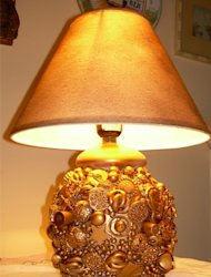 Thrift store lamp and costume jewelry can be transformed into folk art with gold spray paint.