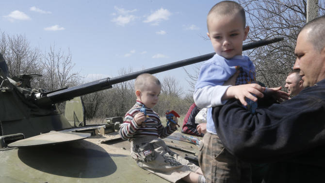 Local residents look at the airborne combat vehicle, which was destroyed during a Ukrainian night combat operation, in the village of Horodychevo, near Kramatorsk, Eastern Ukraine, Friday, April 18, 2014. Ukraine is hoping to placate Russia and calm hostilities with its neighbor even as the U.S. prepares a new round of sanctions to punish Moscow for what it regards as fomenting unrest. (AP Photo/Efrem Lukatsky)