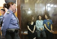 Members of the all-girl punk band Pussy Riot: Nadezhda Tolokonnikova (right), Maria Alyokhina (left) and Yekaterina Samutsevich sit in a glass-walled cage after being sentenced in Moscow on August 17