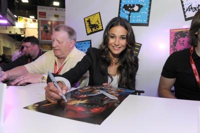 "Emmanuelle Chriqui, who voices Cheetara, signs posters at a ""Thundercats"" event -- Warner Bros"