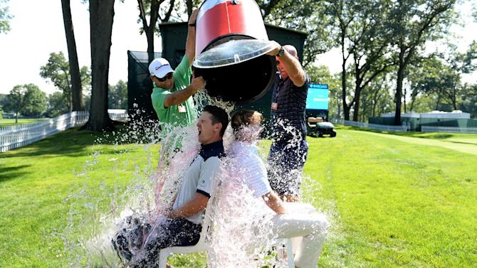 Justin Rose of England and Brandt Snedeker of the USA take the 'ice bucket challenge' with a bit of help from their caddies after a practice round prior to The Barclays on August 19, 2014 in Paramus, New Jersey