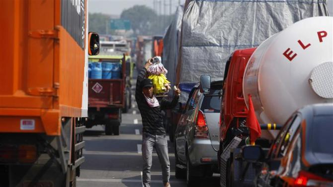 A street vendor looks for customer during a traffic jam in Jakarta