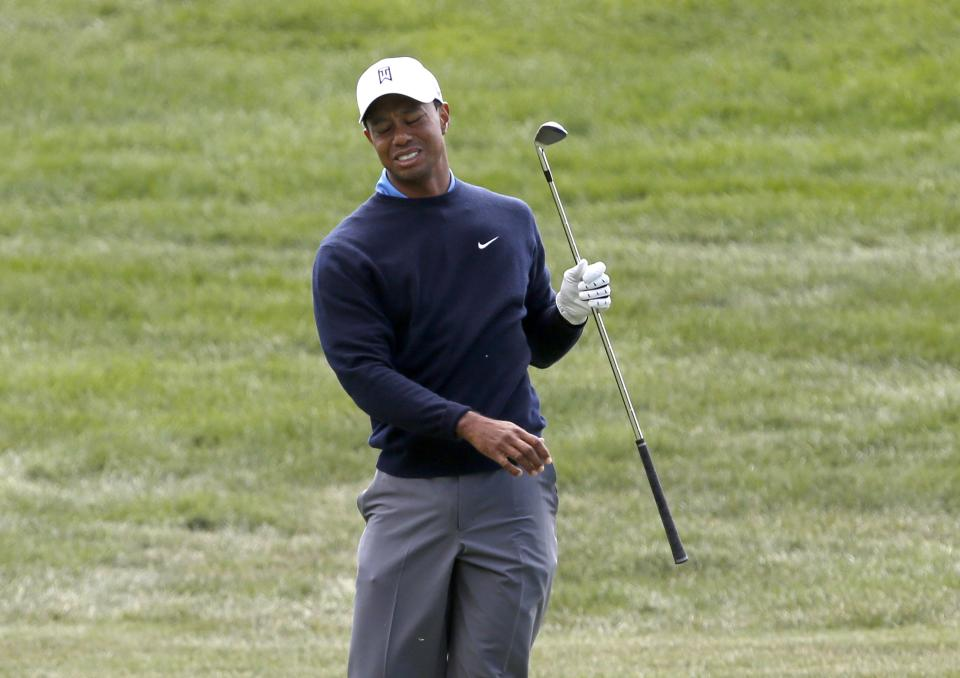 Tiger Woods reacts after hitting his approach shot on the first fairway under trees behind the hole during the second round of the BMW Championship golf tournament at Conway Farms Golf Club in Lake Forest, Ill., Friday, Sept. 13, 2013. (AP Photo/Charles Rex Arbogast)