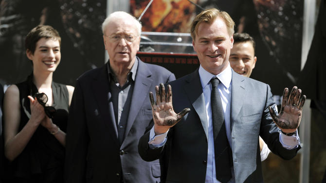 "Christopher Nolan, director of the upcoming film ""The Dark Knight Rises,"" holds up his hands after putting them in cement during a ceremony for him at Grauman's Chinese Theatre on Saturday, July 7, 2012, in Los Angeles. Looking on from left are cast members Anne Hathaway, Michael Caine and Joseph Gordon-Levitt. (Photo by Chris Pizzello/Invision/AP)"