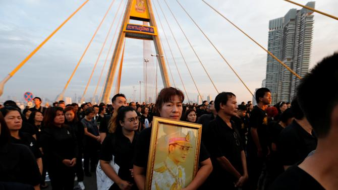 A woman holds a portrait of late Thai King Bhumibol Adulyadej during an event to mark his birthday at Bhumibol Bridge over Chao Phraya river in Bangkok