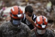 Rescue workers try to recover the body of a landslide victim as a resident reacts in Nova Friburgo, Brazil, Saturday, Jan. 15, 2011. After four nights of torrential rains, mudslides have killed more than 500 people in the Rio de Janeiro area.