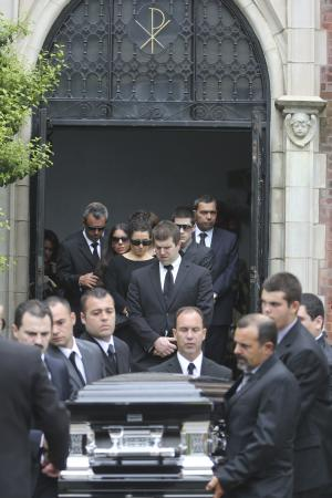 FILE - In this May 22, 2013, file photo, Andrea Rebello's father Fernando, left, twin sister Jessica, second from left and mother Nella, third from left, follow Rebello's casket after her funeral service at St. Teresa of Avila Church in Sleepy Hollow, N.Y. A Long Island district attorney has decided not to prosecute a police officer who killed the Hofstra University student and the armed intruder who was holding her hostage. Nassau County District Attorney Kathleen Rice issued a 28-page report Wednesday, April 2, 2014, stating that a prosecution of Police Officer Nikolas Budlimic is not warranted. Budlimic fired at the intruder who was holding Rebello in a headlock when he was the first officer to arrive at the report of a home invasion in 2013. One round missed the intruder but struck and killed Rebello by mistake. (AP Photo/Mary Altaffer, File)