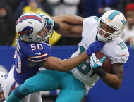 Buffalo Bills middle linebacker Kiko Alonso (50) tackles Miami Dolphins wide receiver Rishard Matthews (18) during the second half of an NFL football game Sunday, Dec. 22, 2013, in Orchard Park, N.Y. (AP Photo/Bill Wippert)