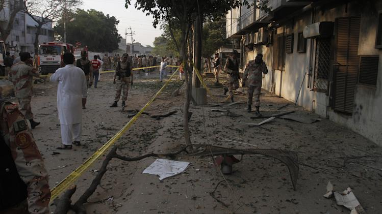 Troops of Pakistan's paramilitary force and investigators gather at the site of an explosion in Karachi, Pakistan on Thursday, Nov. 8, 2012. A suicide bomber smashed a truck packed with explosives into housing for a paramilitary force protecting Pakistan's largest city, killing at least one person in the explosion Thursday morning that sent a large plume of smoke into the sky, officials said. (AP Photo/Shakil Adil)