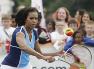 U.S. first lady Michelle Obama plays tennis with schoolchildren during a &#39;Let&#39;s Move!&#39; event for about 1,000 American military children and American and British students at the U.S. ambassador&#39;s residence in London, ahead of the 2012 Summer Olympics, Friday, July 27, 2012. (AP Photo/Lefteris Pitarakis)