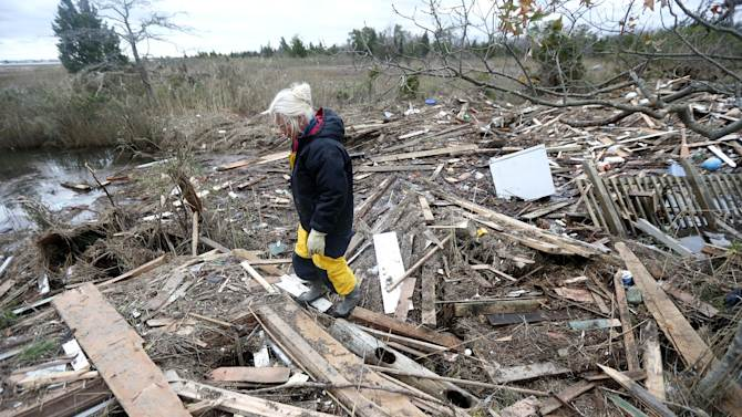 Tricia Burke walks over debris which washed up onto her property in the wake of superstorm Sandy, Thursday, Nov. 1, 2012, in Brick, N.J. Three days after Sandy slammed the mid-Atlantic and the Northeast, New York and New Jersey struggled to get back on their feet, the U.S. death toll climbed to more than 80, and more than 4.6 million homes and businesses were still without power. (AP Photo/Julio Cortez)
