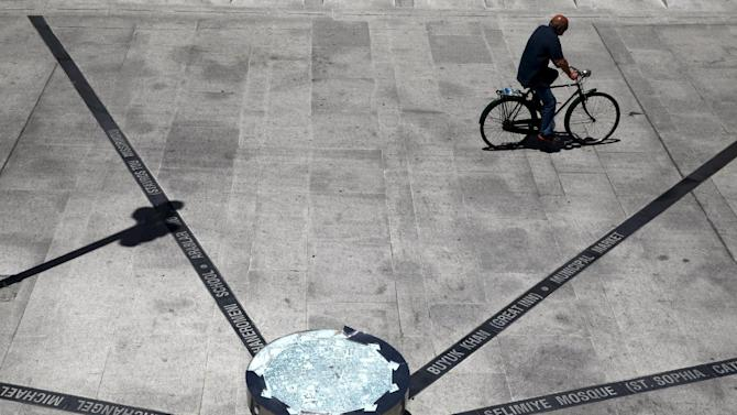 Man rides his bicycle next to a paved map pointing to historical sites in Nicosia