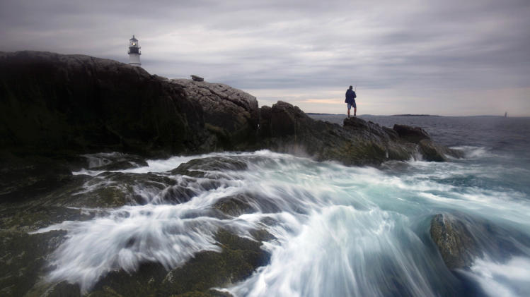 FILE - This July 25, 2011 file photo shows the surf crashing on the rocks as a man fishes for striped bass below Portland Head Light at Fort Williams Park in Cape Elizabeth, Maine. This lighthouse in Cape Elizabeth, complete with a museum and a gift shop, has been called one of the most-photographed lighthouses in the country. Commissioned by George Washington, the light went into service in 1791. It became automated in 1989 and is now owned by the town of Cape Elizabeth. The lighthouse is the premier attraction at Fort Williams Park, a six-mile drive from Portland.  (AP Photo/Robert F. Bukaty, file)