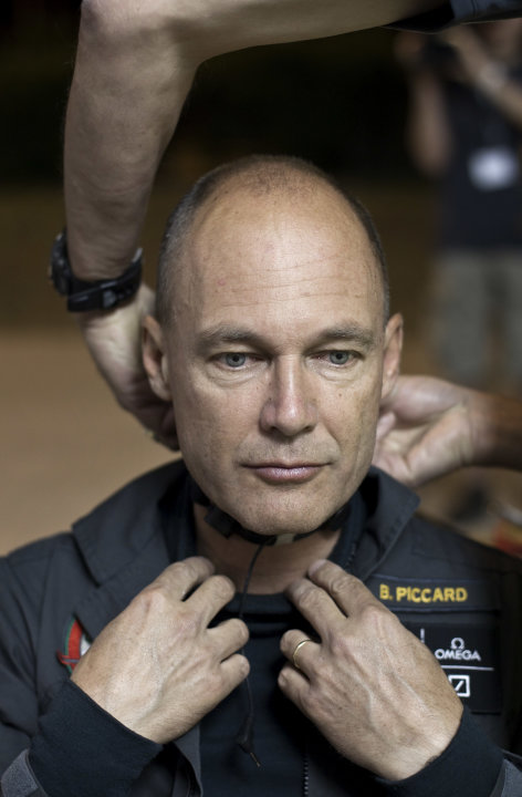 Solar Impulse pilot Bertrand Piccard is helped to fit his flying suit at Barajas airport in Madrid, Spain, Tuesday, June 5, 2012. The experimental solar-powered airplane arrived in Madrid on May 25, 2