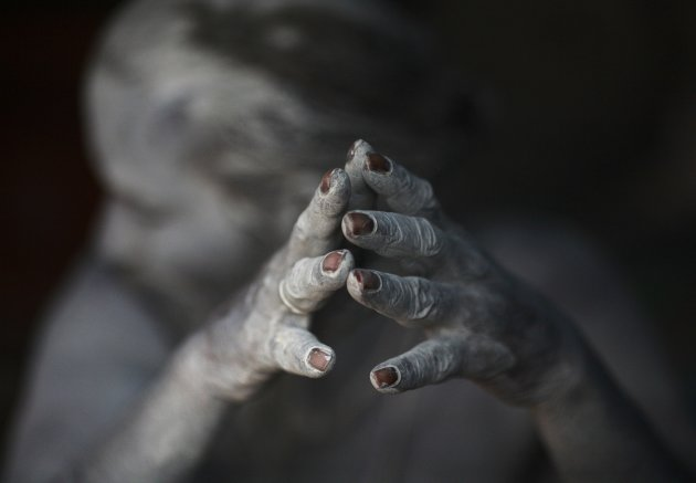 Ash-encrusted hands of a sadhu are seen as he sits beside a fire after applying ashes to his face and body at his ashram on the premises of Pashupatinath Temple in Kathmandu