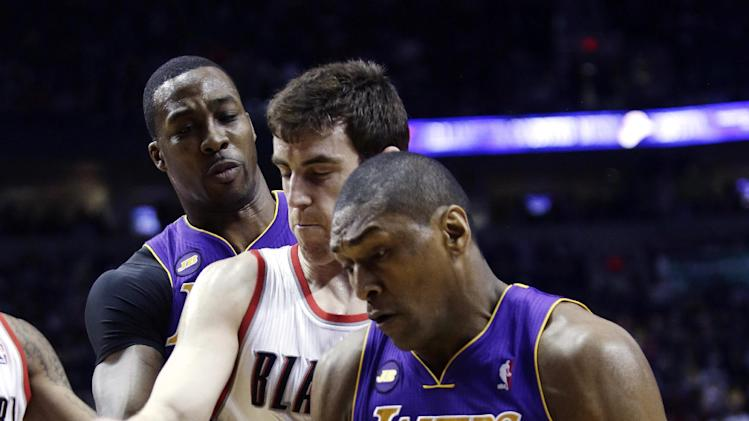 Los Angeles Lakers center Dwight Howard, left, passes inside to forward Metta World Peace, right, past Portland Trail Blazers forward Victor Claver, from Spain, during the first quarter of an NBA basketball game in Portland, Ore., Wednesday, April 10, 2013.(AP Photo/Don Ryan)