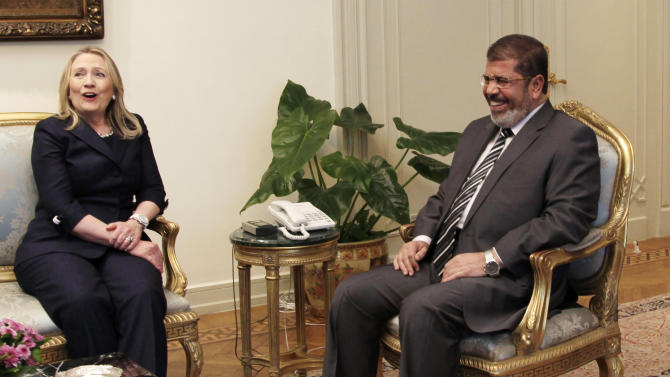 U. S. Secretary of State Hillary Clinton, left, and Egyptian President Mohammed Morsi laugh during a photo opportunity at their meeting at the Presidential palace in Cairo, Egypt, Saturday, July 14, 2012. (AP Photo/Maya Alleruzzo)