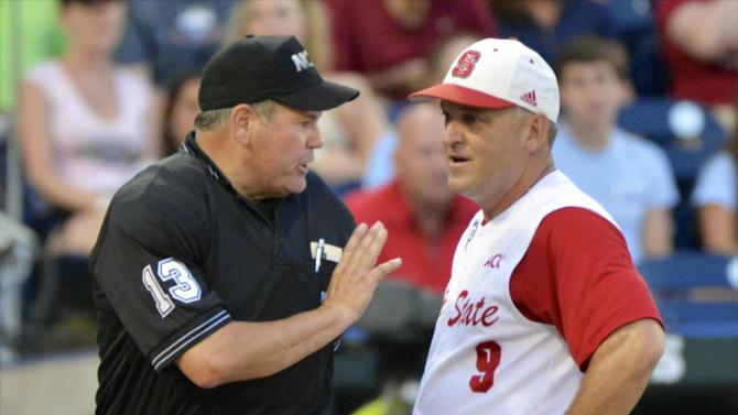 North Carolina State coach Elliott Avent, right, tries to appease home plate umpire Joe Burleson after a North Carolina State pitcher spiked his glove in reaction to a score by North Carolina's Brian Holberton in the fourth inning of an NCAA College World Series elimination baseball game in Omaha, Neb., Thursday, June 20, 2013. (AP Photo/Ted Kirk)