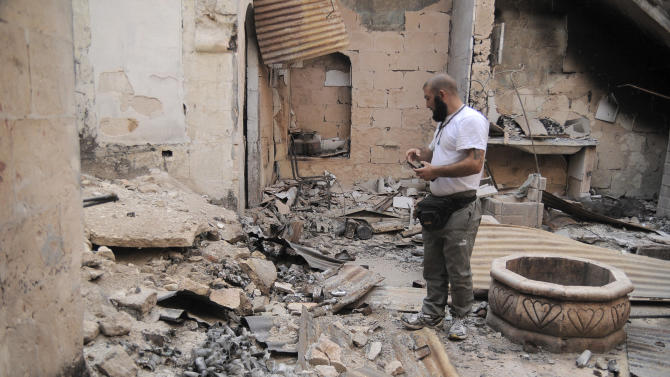 In this Tuesday, Nov. 6, 2012 photo, a Syrian rebel stands in the ruins of a private house, destroyed by shelling and fighting, in the Old City of Aleppo, Syria, now controlled by the Free Syrian Army.(AP Photo/Monica Prieto)
