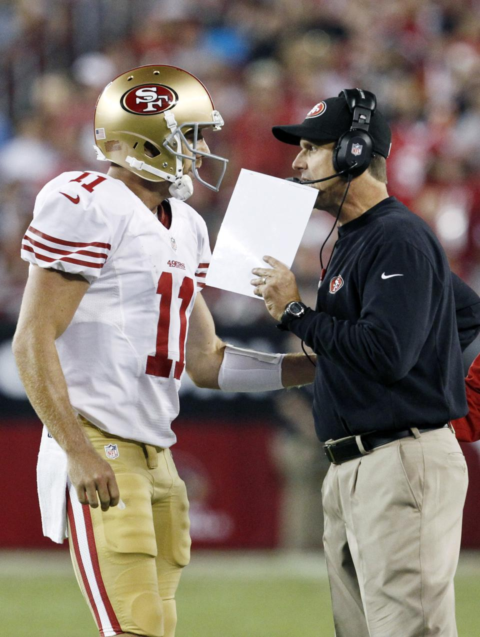 San Francisco 49ers head coach Jim Harbaugh, right, talks with Alex Smith (11) during a timeout in the first half of an NFL football game against the Arizona Cardinals Monday, Oct. 29, 2012, in Glendale, Ariz. (AP Photo/Ross D. Franklin)