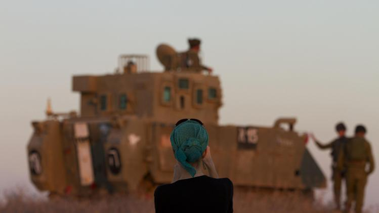 "A woman photographs Israeli soldiers on top an armored personal carrier close to the Israel Gaza Border, southern Israel,Thursday, Nov. 15, 2012. Israel's prime minister says the army is prepared for a ""significant widening"" of its operation in the Gaza Strip. Benjamin Netanyahu told reporters on Thursday that Israel has ""made it clear"" it won't tolerate continued rocket fire on its civilians. (AP Photo/Ariel Schalit)"