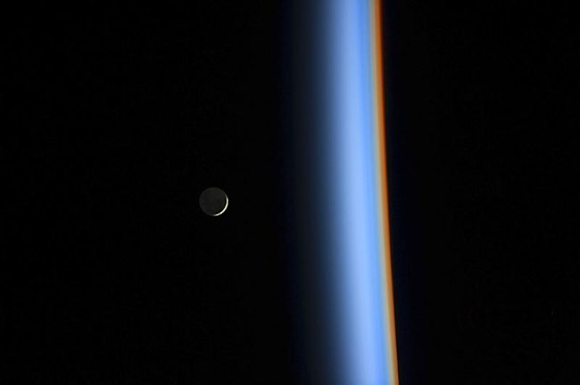 A crescent moon rises over the cusp of the Earth's atmosphere in this picture by Japan Aerospace Exploration Agency astronaut Koichi Wakata onboard th...
