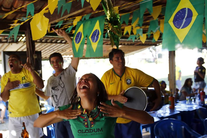 Brazil soccer fans react as they watch their team's victory against Chile in a bar in Brasilia