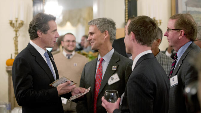 "New York Gov. Andrew Cuomo, left, talks to visitors to the Executive Mansion as part of a ""Wine, Beer and Spirits Summit"" on Wednesday, Oct. 24, 2012, in Albany, N.Y. The aim of the summit is to boost wine production and craft brewers, in part to spur job growth. Visitors to the mansion were able to sample products from around New York state. (AP Photo/Mike Groll)"