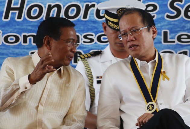 Philippine President Aquino listens as Vice President Binay speaks to him during ceremonies marking the Philippine Navy's 115th anniversary celebrations in Fort San Felipe