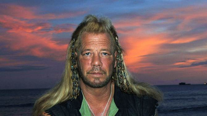 """FILE - This Jan. 10, 2006 file photo shows bounty hunter Duane """"Dog"""" Chapman star of the Hawaii-based reality show, """"Dog the Bounty Hunter,"""" on Waikiki Beach, in Honolulu. Chapman has his bags packed for London, but a murder conviction from the late 1970s is keeping him out of the United Kingdom. He was to appear on another reality show, """"Celebrity Big Brother,"""" but he has been denied a visa. """"It's something that follows you the rest of your life, no matter who you become or who you are,"""" Chapman, 59, said Monday from Honolulu, where he lives. """"I'm not proud of it."""" (AP Photo/Lucy Pemoni, file)"""