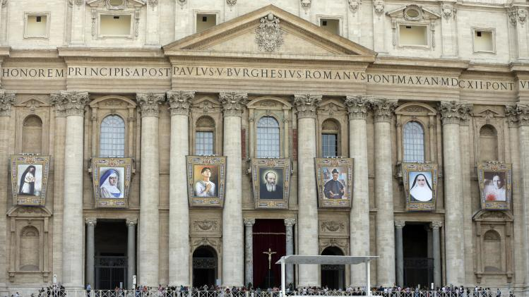 Tapestries of saints-to-be from left; Kateri Tekakwitha, Maria del Carmen, Pedro Calungsod, Jacques Berthieu, Giovanni Battista Piamarta, Mother Marianne Cope, and Anna Shaeffer hang from St. Peter's Basilica at the Vatican, Friday, Oct. 19, 2012. The seven will be declared saints in a ceremony presided over by Pope Benedict XVI on Sunday. (AP Photo/Alessandra Tarantino)