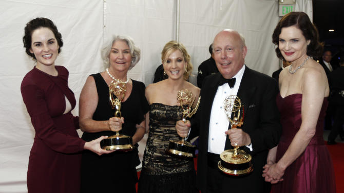 "Michelle Dockery, far left, Joanne Froggatt, third from left, Julian Fellowes, fourth from left, and Elizabeth McGovern, right, are seen backstage with the award for outstanding miniseries or movie for ""Downton Abbey"" at the 63rd Primetime Emmy Awards on Sunday, Sept. 18, 2011 in Los Angeles. (AP Photo/Matt Sayles)"