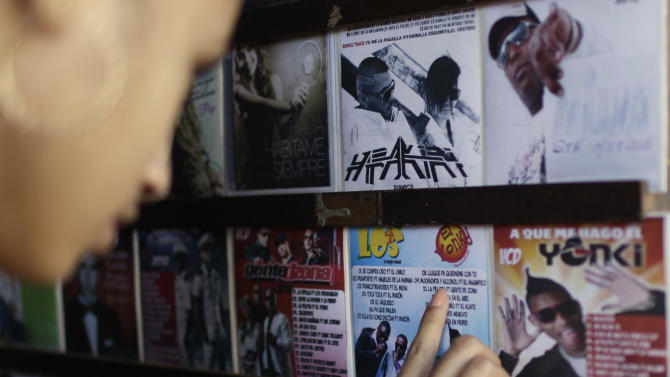 "In this Jan. 4, 2013 photo, Yadisbel Ruiz, 17, reads the titles of songs on a reggaeton album at a music and movie store run from a home in Havana, Cuba. Cuban authorities have recently announced restrictions reportedly declaring state-run recording studios and broadcasts off-limits to songs with questionable lyrics. They also prohibit such music in performance spaces subject to government control. The rules would theoretically apply to all genres, but it's reggaeton that leading cultural lights have singled out for criticism in official media while warning of new rules governing ""public uses of music."" (AP Photo/Franklin Reyes)"
