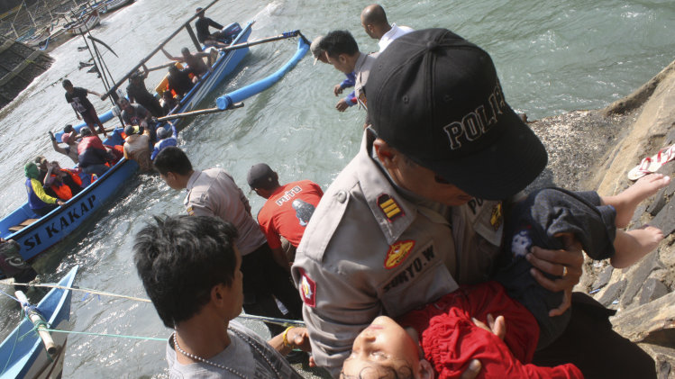 A police officer carries a child who appears to be unconscious after a boat carrying asylum seekers sank off Java island, in Cianjur, West Java, Indonesia, Wednesday, July 24, 2013. Rescuers were searching Wednesday for dozens of asylum seekers still believed missing after their boat sank in Indonesian waters on the way to Australia. More than 150 survivors were brought to safety and three bodies were recovered. (AP Photo)
